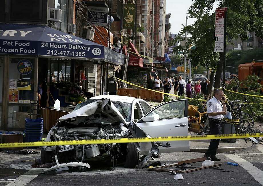 A car damaged in an accident sits in the middle of the street in the East Village section of New York, Wednesday, June 19, 2013.  Fire authorities say eight people have been hurt, several of them seriously, after a car jumped a curb and slammed into a 24-hour grocery around 7 a.m. Wednesday. A witness says the driver lost control about a block away and plowed through everything on the sidewalk.  (AP Photo/Seth Wenig) Photo: Seth Wenig, Associated Press