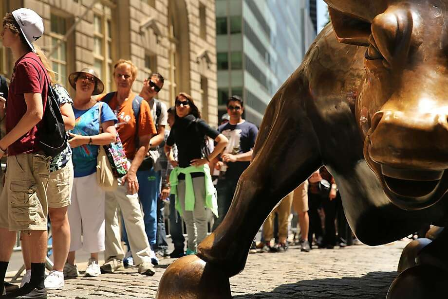 NEW YORK, NY - JUNE 19: People wait in line to take a picture with the bronze bull in the Financial district which has become a Wall Street icon during afternoon trading on June 19, 2013 in New York City. Following news that the Federal Reserve will leave interest rates unchanged, the Dow Jones industrial average and S&P 500 dropped 0.6%.  (Photo by Spencer Platt/Getty Images) Photo: Spencer Platt, Getty Images