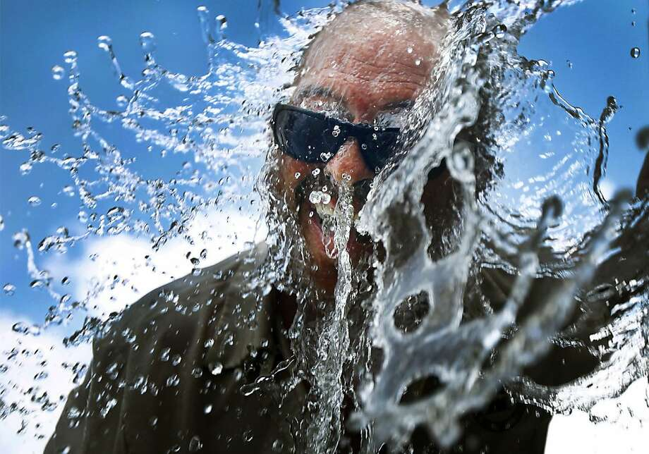 Bartlett Parks and Recreation Department employee Olen Nails cools off under a stream of water Wednesday, June 19, 2013 while helping to fill Flaherty Municipal Center pond with catfish for next weekend's fish rodeo in Bartlett, Tenn. The warm weather is expected to continue through the weekend with little chance of rain to help cool off.  (AP Photo/The Commercial Appeal, Mark Weber) Photo: Mark Weber, Associated Press