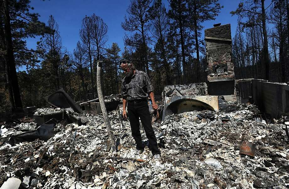 Eric Olson sorts through the remains of belongings Wednesday, June 19, 2013, while visiting their destroyed home on Shoup Road in Black Forest north of Colorado Springs, Colo. (AP Photo/The Gazette, Christian Murdock) Photo: Christian Murdock, Associated Press