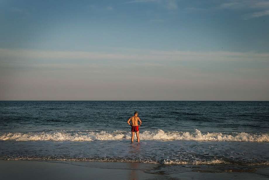 SHIRLEY, NY - JUNE 19:  A man walks into the water at Smith Point Beach, near the TWA 800 International Memorial, which is dedicated to the 230 people who died from an explosion on flight TWA 800 in 1996, on June 19, 2013 in Shirley, New York. The flight was enroute to Paris when an explosion killed everyone on board. The reason for the explosion has been a source of controversy since the tragedy and a new documentary suggests the final conclusions of the official investigation into the explosion may have been incorrect.  (Photo by Andrew Burton/Getty Images) Photo: Andrew Burton, Getty Images
