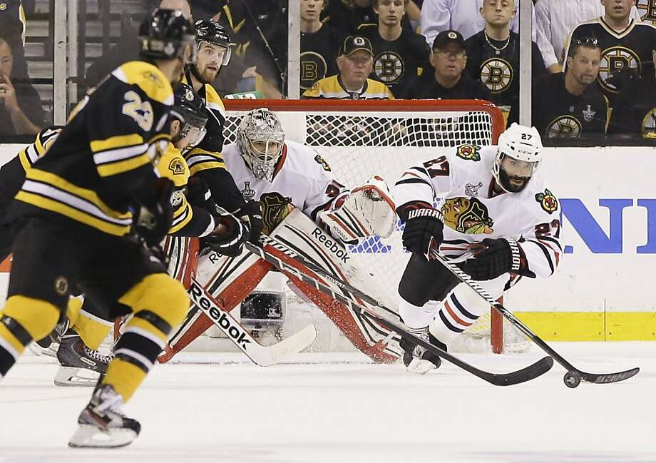 Chicago Blackhawks defenseman Johnny Oduya (27), of Sweden, pokes the puck in front of Chicago Blackhawks goalie Corey Crawford (50) and Boston Bruins center Chris Kelly (23) during the first period in Game 4 of the NHL hockey Stanley Cup Finals, Wednesday, June 19, 2013, in Boston. (AP Photo/Elise Amendola) Photo: Elise Amendola, Associated Press