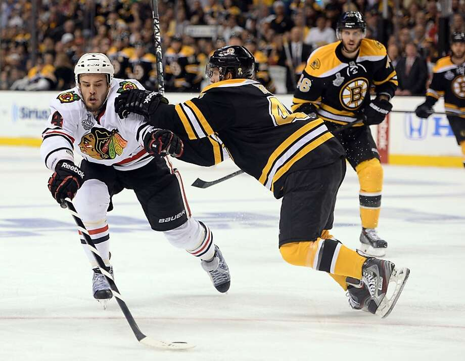BOSTON, MA - JUNE 19: David Krejci #46 of the Boston Bruins defends Niklas Hjalmarsson #4 of the Chicago Blackhawks in Game Four of the 2013 NHL Stanley Cup Final at TD Garden on June 19, 2013 in Boston, Massachusetts.  (Photo by Harry How/Getty Images) Photo: Harry How, Getty Images