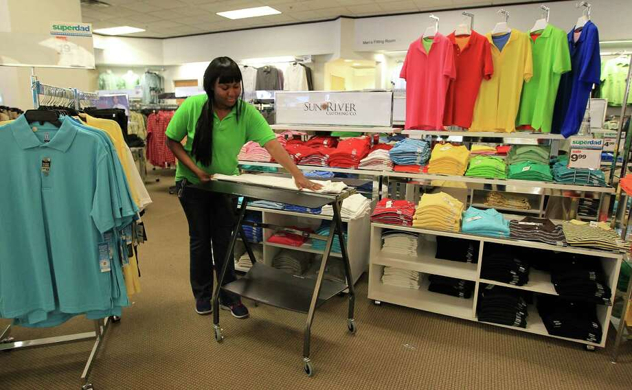 Brittinee Johnson folds clothes at a Palais Royal in Meyerland Plaza. The owner of the Palais Royal chain will pay double time to its employees who work on Thanksgiving.  Photo: Karen Warren, Staff / © 2013 Houston Chronicle