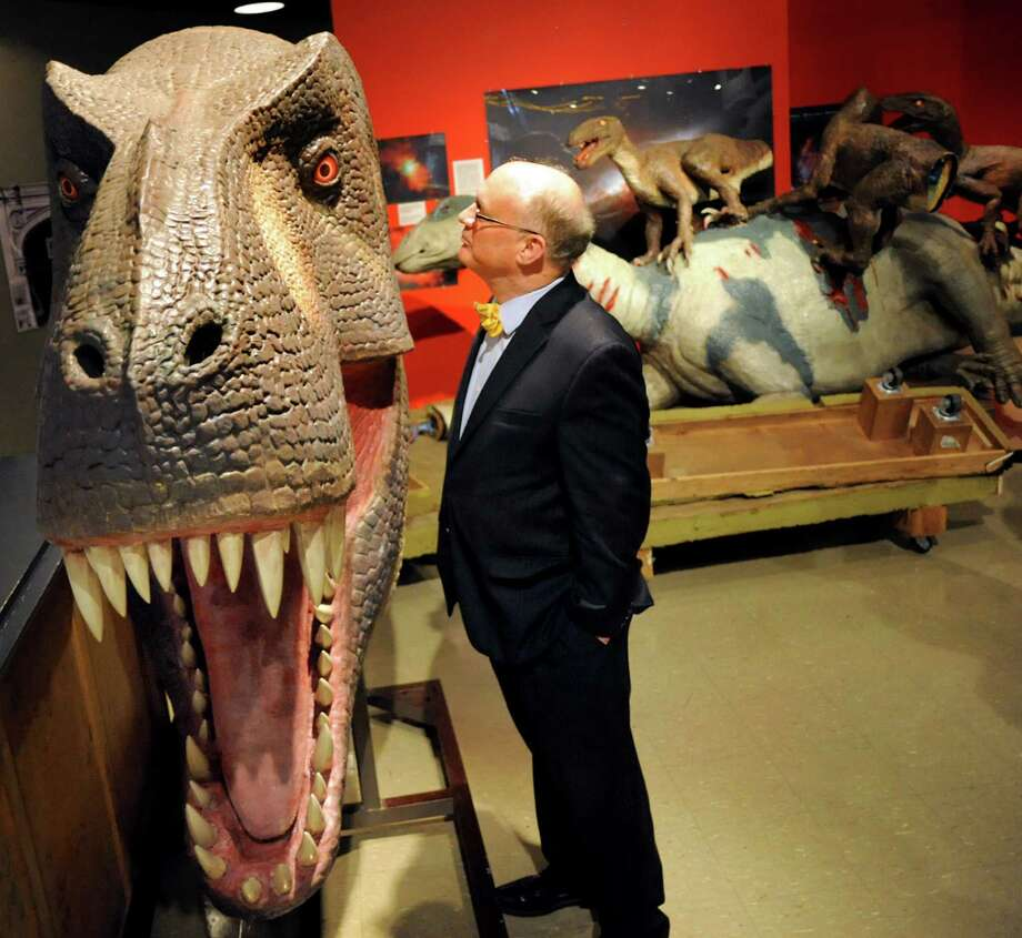 """Executive director William """"Mac"""" Sudduth studies the head of a Tyrannosaurus rex on Wednesday, June 19, 2013, at miSci in Schenectady, N.Y. The traveling Dinosaurs! exhibit arrived at the museum for installation, and features 17 animatron dinosaurs and seven interactive stations such as dino dig boxes and fossil rubbings. The exhibit runs from June 29 to Sept. 29 and is included in general admission to the museum of innovation and science. Prices are $6.50 for children, $8 for seniors and $9.50 for adults. (Cindy Schultz / Times Union) Photo: Cindy Schultz / 00022883A"""