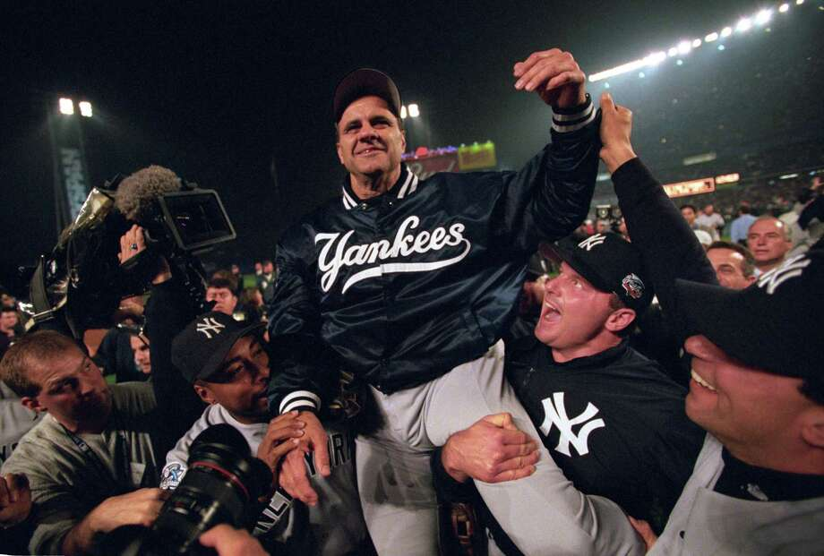 Baseball: World Series. New York Yankees manager Joe Torre victorious, getting carried off field after winning game vs New York Mets at Shea Stadium.
