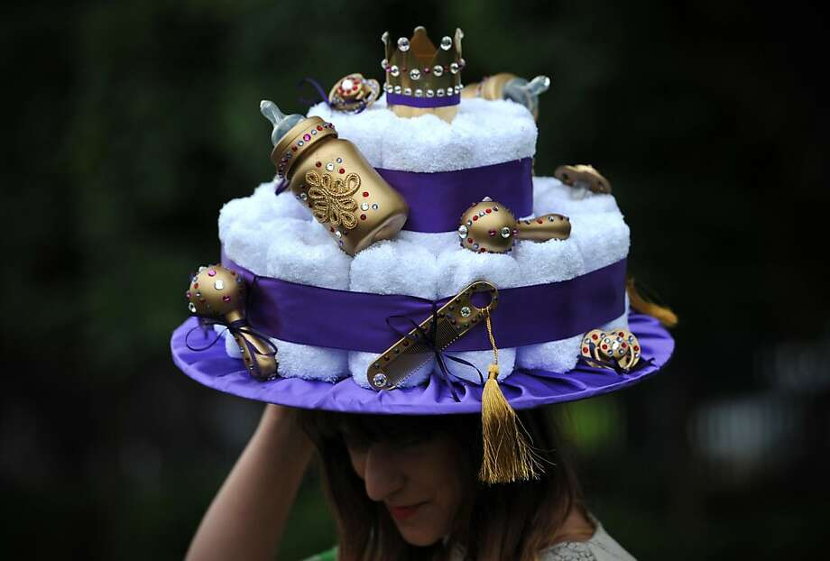 A woman poses for a photograph in a royal baby-themed hat during the third day of Royal Ascot, in Berkshire, west of London, on June 20, 2013.  Photo: Carl Court, AFP/Getty Images