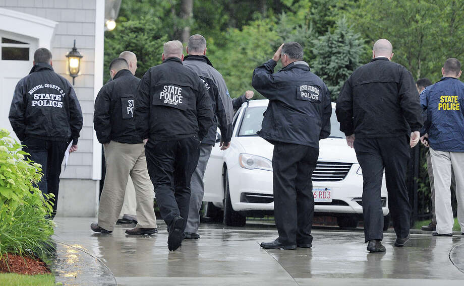 In this Tuesday, June 18, 2013 photo, state and local police gather outside the home of New England Patriot's NFL football player Aaron Hernandez in North Attleborough, Mass.  Police spent hours at the home Tuesday as another group of officers searched an industrial park about a mile away where a body was discovered the day before.  (AP Photo/The Sun Chronicle, Martin Gavin) Photo: Martin Gavin, Associated Press / The Sun Chronicle