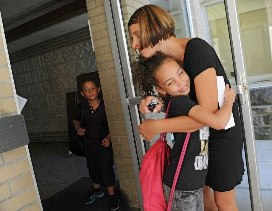 Second grader Si'mya Brand, 7, of Schenectady gets a goodbye hug from her teacher Gina Mell as the Elmer Avenue Elementary School is let out for the summer on Thursday, June 20, 2013 in Schenectady, N.Y.  (Lori Van Buren / Times Union) Photo: Lori Van Buren / 00022893A