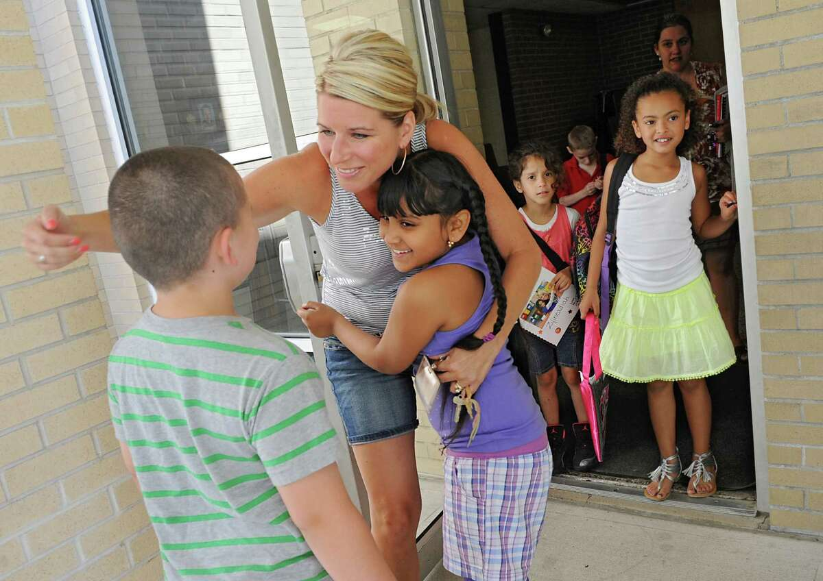 Second grade teacher Kari Altieri gives her students Tyris Smith, 8, left, and Jasoda Somwaru, 8, both of Schenectady, a hug goodbye as the Elmer Avenue Elementary School is let out for the summer on Thursday, June 20, 2013 in Schenectady, N.Y. (Lori Van Buren / Times Union)