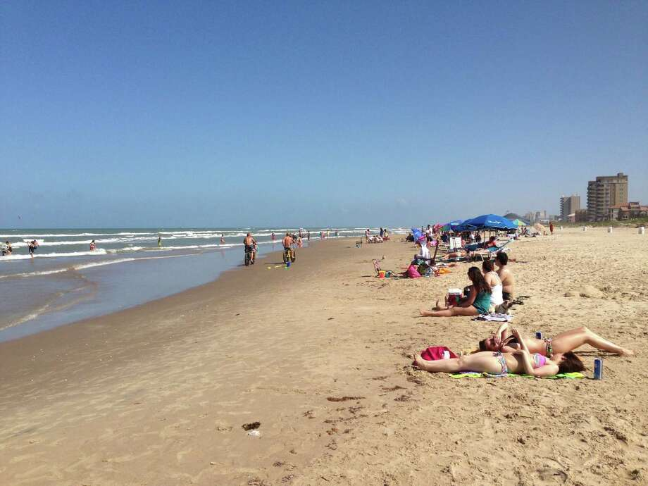 Travelers worship the sun, people-watch and romp in the surf along the pristine beach at South Padre Island. Photo: Carla Nelson / For The Express-News
