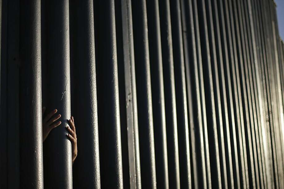 On the border: Daniel Zambrano of Tijuana grasps one of the bars that make up the wall separating the
