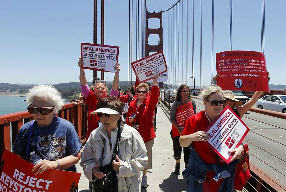 Nurses, many clad in red scrubs, cross the Golden Gate Bridge to press President Obama to stop the pipeline project. Photo: Michael Macor, The Chronicle