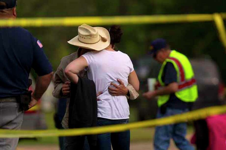 Mike and April Davis mother and father of Devin Davis embrace as local authorities including Houston police divers along with Texas Equusearch search for 2-year-old Devin Davis who went missing yesterday afternoon while his mother was taking a nap in Liberty County east of Cleveland Wednesday, March 28, 2012, in Cleveland. 