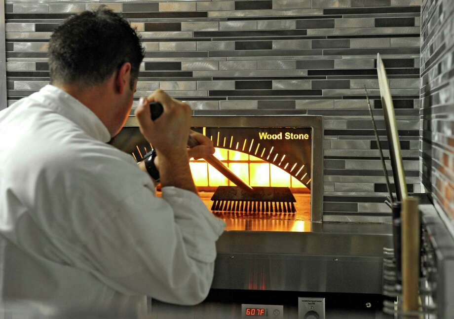 Tala American Bistro. 626 New Loudon Rd., Latham.Chef Eric Tisaj uses a brush to clean the wood stone oven at Tala American Bistro on Thursday, June 13, 2013 in Latham, N.Y. (Lori Van Buren / Times Union) Photo: Lori Van Buren / 00022785A