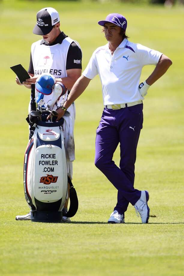 CROMWELL, CT - JUNE 20:  Rickie Fowler (R) stands by his golf bag during the first round of the Travelers Championship held at TPC River Highlands on June 20, 2013 in Cromwell, Connecticut.  (Photo by Michael Cohen/Getty Images)