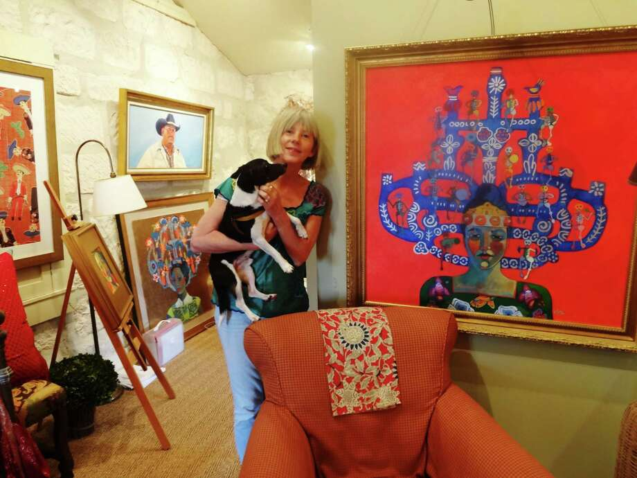 "Kathy Sosa takes a break in a Southtown studio. Next to her is one of the paintings from her ""Trees of Life"" series, which is among her works exhibited at Semmes Library through June 31. Photo: Lydia Duncombe / San Antonio Express-News"