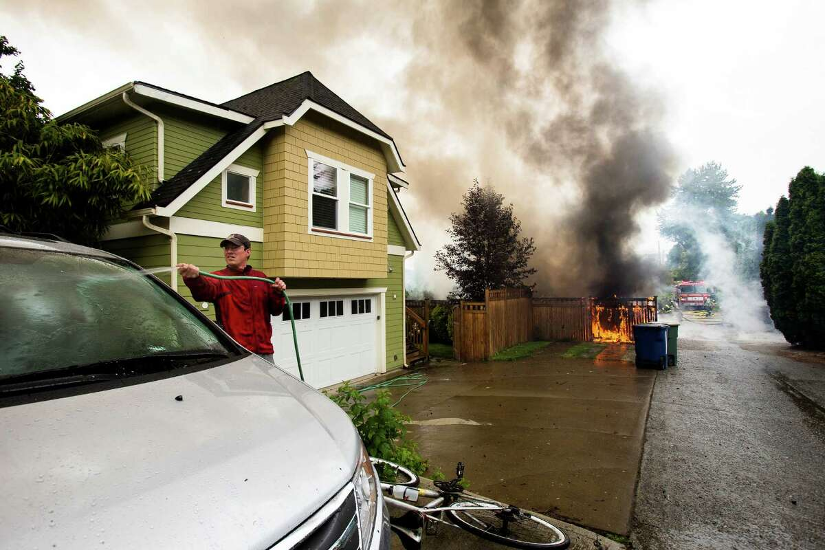 A next door neighbor waters down his car for protection as firefighters battle a garage blaze that left several other cars destroyed with no reported injuries Thursday, June 20, 2013, on 22nd Avenue West in the Magnolia neighborhood of Seattle. The plume of smoke from the fire could be seen for miles.
