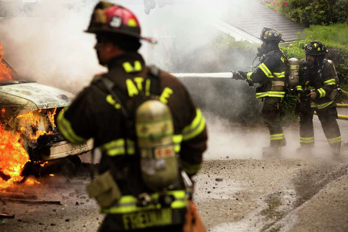 Firefighters battle a garage blaze that left several cars destroyed with no reported injuries Thursday, June 20, 2013, on 22nd Avenue West in the Magnolia neighborhood of Seattle. The fire was quickly put out. The plume of smoke from the fire could be seen for miles.