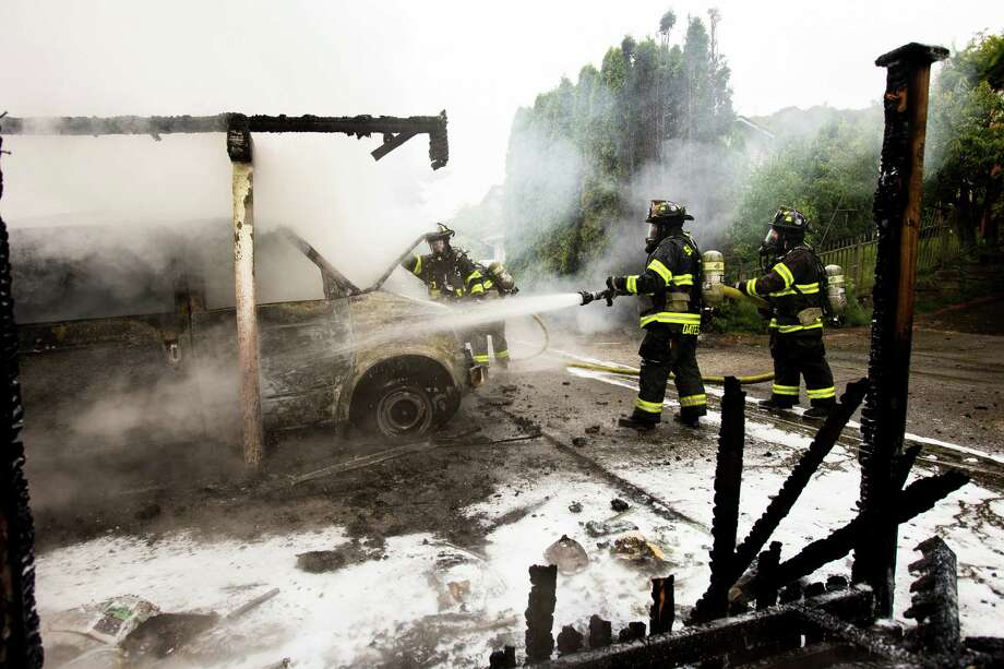 Firefighters battle a garage blaze that left several cars destroyed with no reported injuries Thursday, June 20, 2013, on 22nd Avenue West in the Magnolia neighborhood of Seattle. The plume of smoke from the fire could be seen for miles. Photo: JORDAN STEAD, SEATTLEPI.COM / SEATTLEPI.COM
