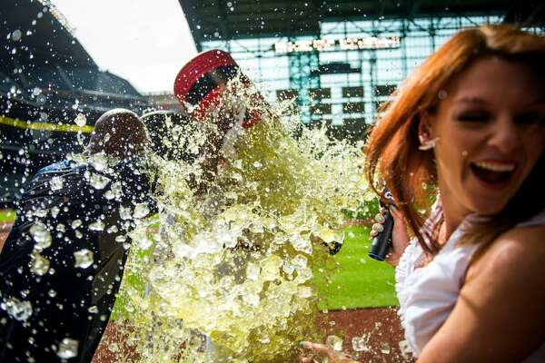 CSN Houston reporter Julia Morales turns away as first baseman Carlos Pena is dunked with Gatorade by Brandon Barnes during his postgame interview after hitting a three-run walk-off home run in the 10th inning.