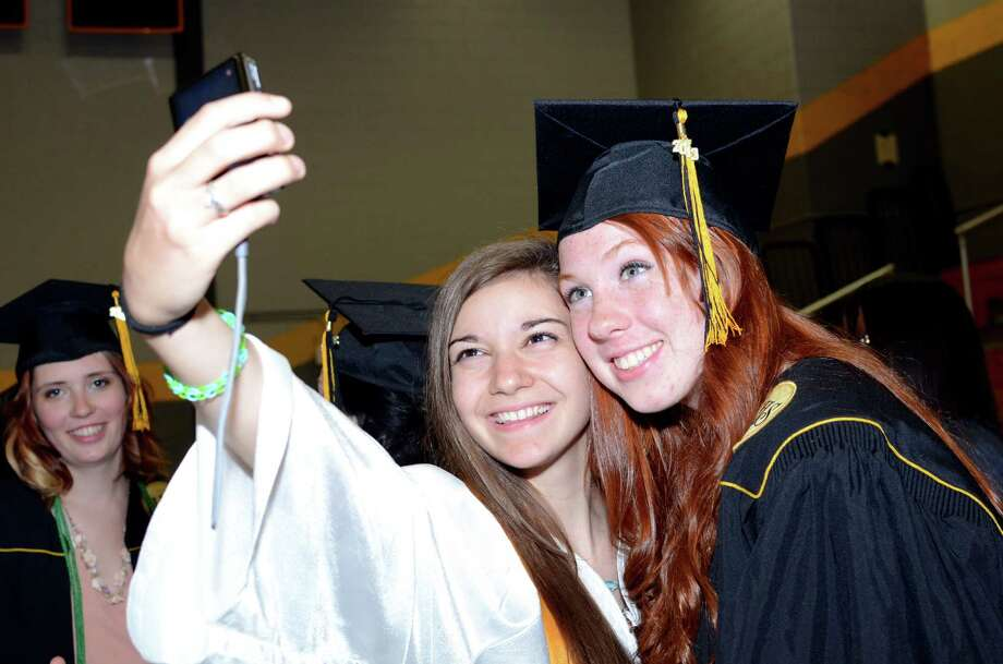 Graduate Laura Campbell, at right, poses for a photo with underclassman Kira Topalian, of the Honor Guard and a junior at Jonathan Law, during the 2013 commencement excercises at Jonathan Law High School in Milford on Thursday, June 20, 2013. Photo: Amy Mortensen / Connecticut Post Freelance