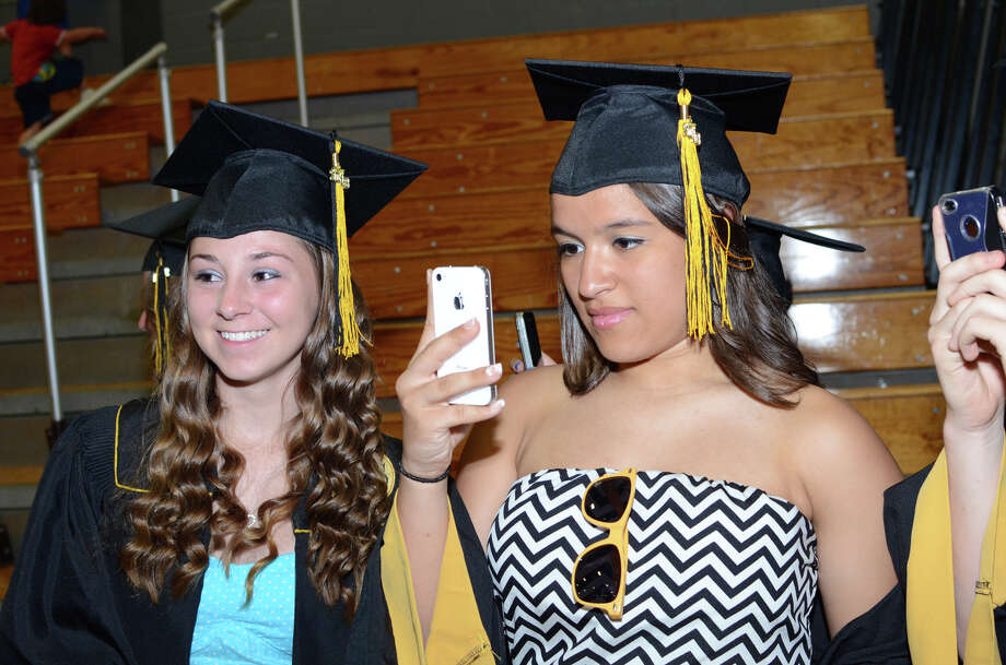 Shaina Jennings watches as Jocelyn Grzywacz, at right, snaps a photo with her phone during the 2013 commencement excercises at Jonathan Law High School in Milford on Thursday, June 20, 2013. Photo: Amy Mortensen / Connecticut Post Freelance