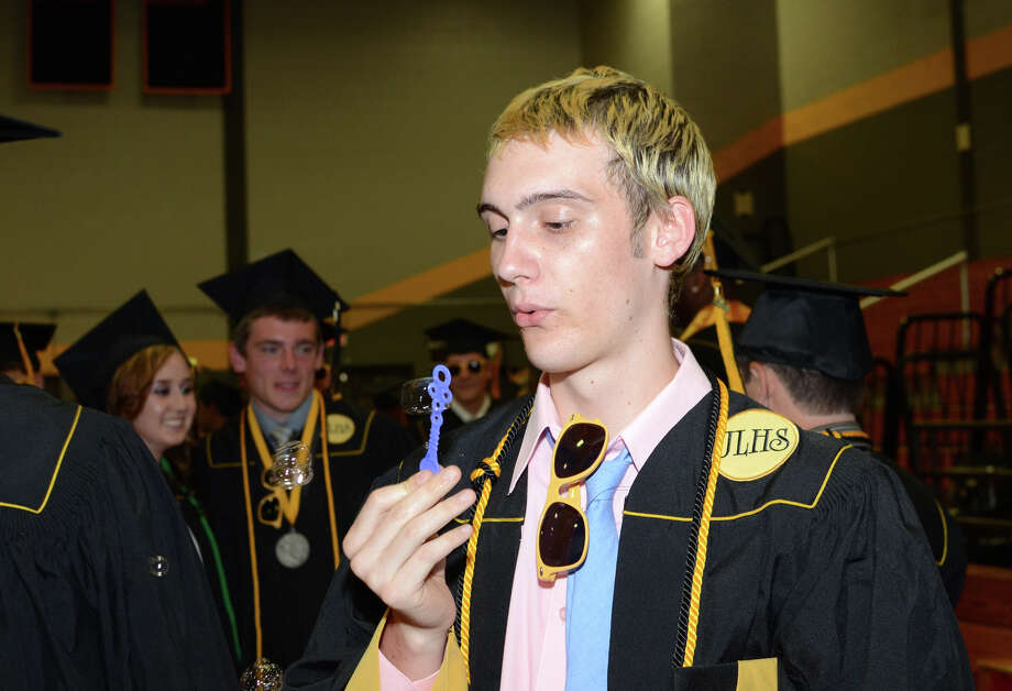 Daniel Ourfalian blows bubbles as he waits in the graduate staging area during the 2013 commencement excercises at Jonathan Law High School in Milford on Thursday, June 20, 2013. Photo: Amy Mortensen / Connecticut Post Freelance