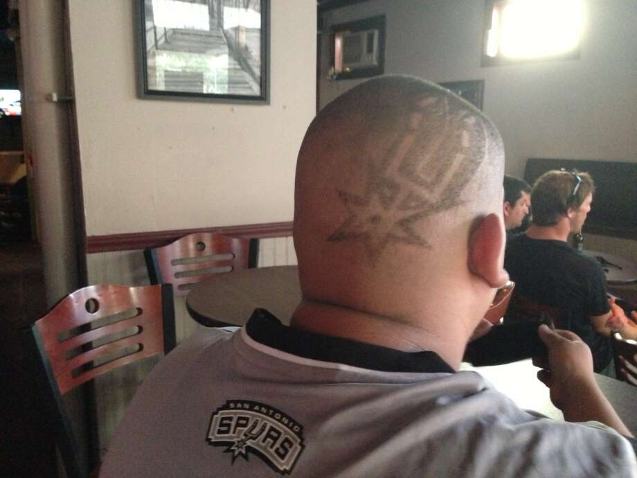 "Angel Hernandez, 26, wasn't messing around with his Spurs style haircut which he got at Acapulco Barber Shop on the West Side when the playoffs started. He had his seat at the Local Bar on Presa Street more than an hour before tipoff. ""We're going to win,"" Hernandez said. ""I had to be downtown for the win."" Photo: Benjamin Olivo / MySA.com"