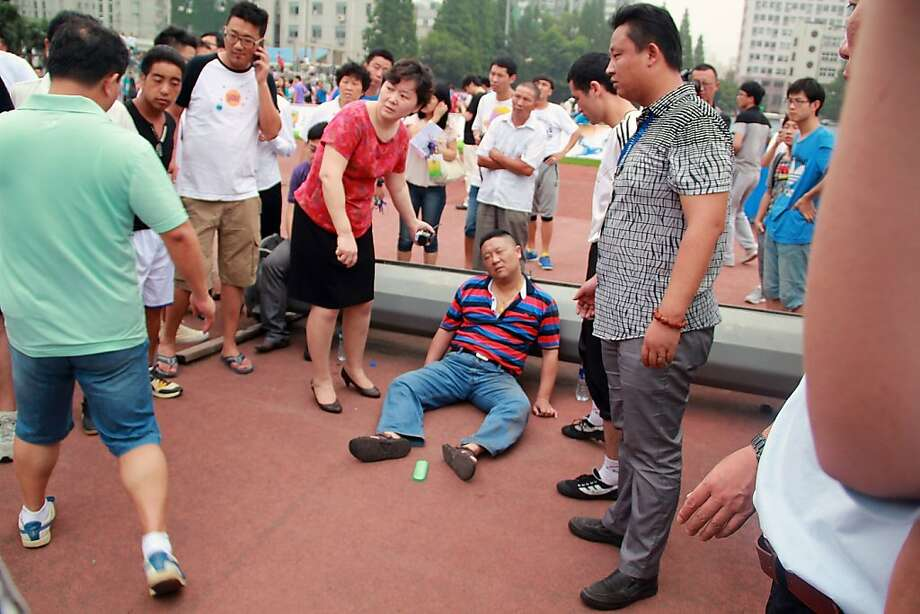 SHANGHAI, CHINA - JUNE 20: (CHINA OUT)  People gather around a man injured in a crush as David Beckham arrives at Tongji University on June 20, 2013 in Shanghai, China. The stampede is reported to have left five people injured and hospitalised. (Photo by Getty Images) Photo: Getty Images