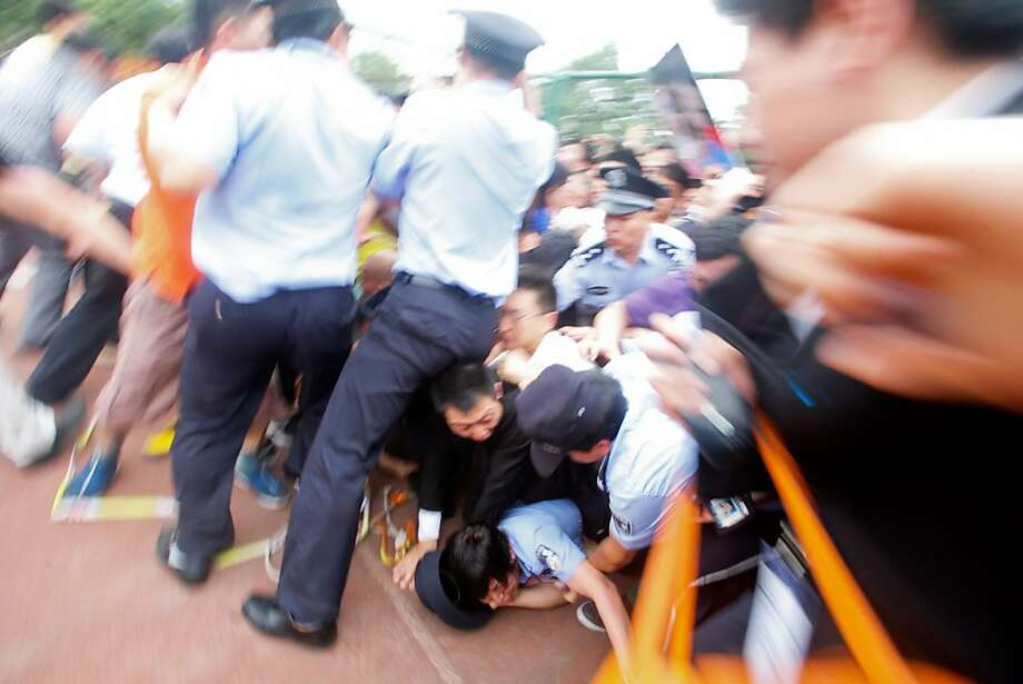 SHANGHAI, CHINA - JUNE 20: (CHINA OUT)  Police officers fail to stop people from falling to the ground in a crush as they surge forward as David Beckham arrives at Tongji University on June 20, 2013 in Shanghai, China. The stampede is reported to have left five people injured and hospitalised. (Photo by Getty Images) Photo: Getty Images