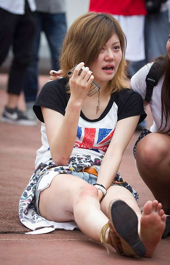 SHANGHAI, CHINA - JUNE 20: (CHINA OUT)  A young woman cries after being caught and hurt in a crush of people as David Beckham arrived at Tongji University on June 20, 2013 in Shanghai, China. The stampede is reported to have left five people injured and hospitalised. (Photo by Getty Images) Photo: Getty Images