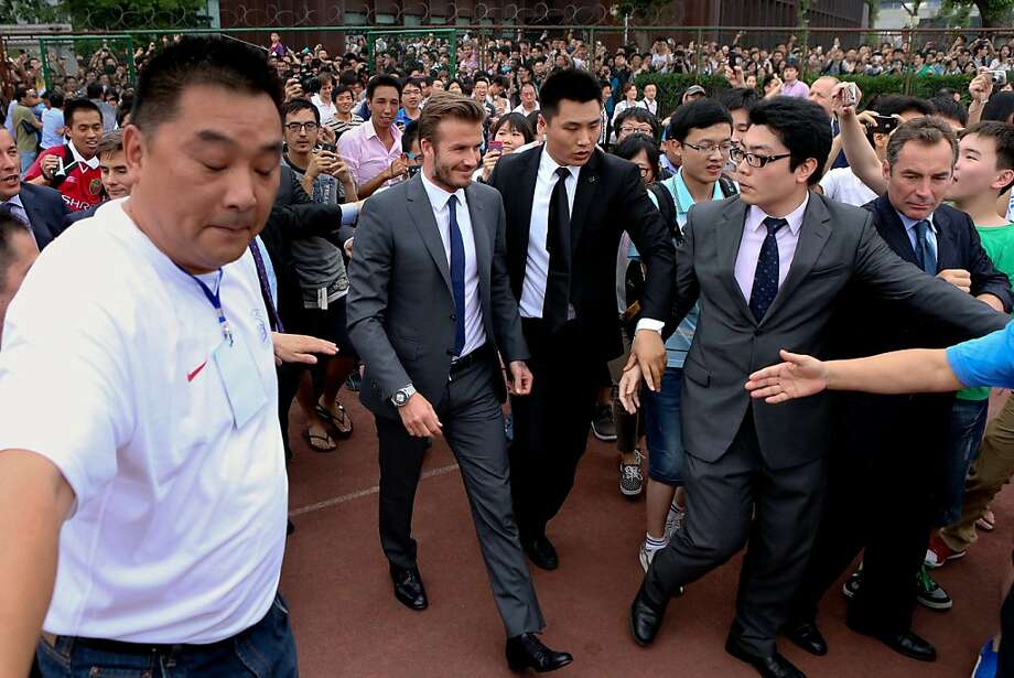 David Beckham walks to meet his fans before a stampede caused by fans storming a security cordon in a university in Shanghai Thursday June 20, 2013. Fans eager to see the soccer superstar stormed a police cordon in a stampede that injured seven people including five security personnel. (AP Photo) CHINA OUT Photo: Associated Press