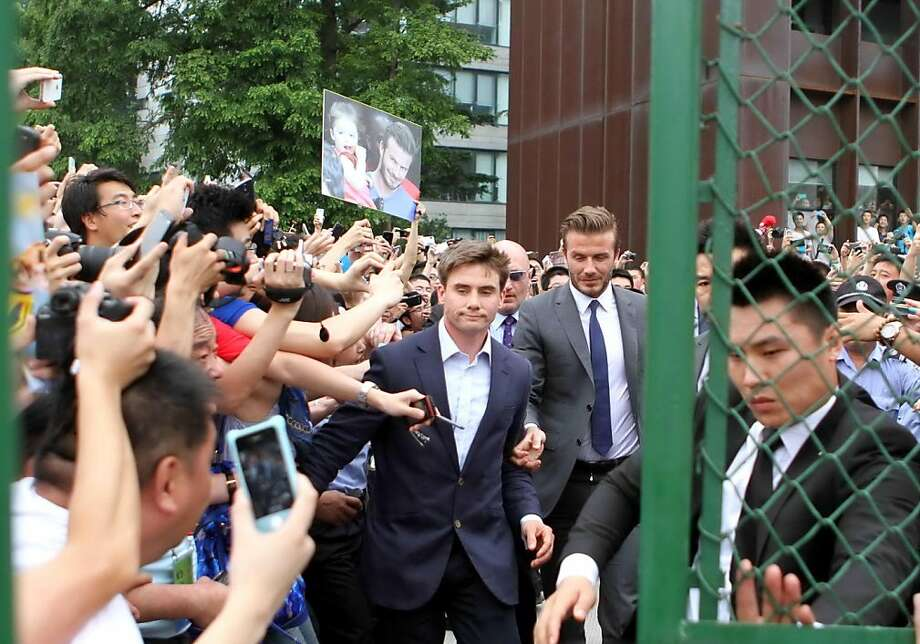Football superstar David Beckham (C) is escorted by security personnel at Tonji University in Shanghai on June 20, 2013. Seven people were hurt in a stampede on June 20 as hundreds of fans rushed to see football superstar David Beckham at an event in China's commercial hub Shanghai, police and local media said.    CHINA OUT     AFP PHOTOSTR/AFP/Getty Images Photo: Str, AFP/Getty Images