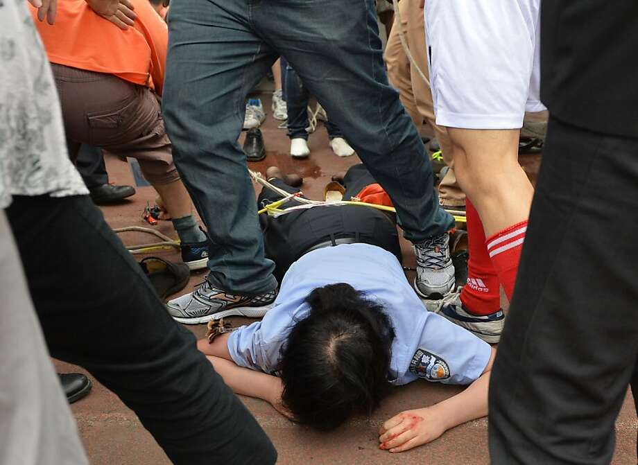 """TOPSHOTS A policewoman (C) lies injured after being crushed in a stampede to see football superstar David Beckham at Tonji University in Shanghai on June 20, 2013. Beckham's visit to China turned """"chaotic"""" on June 20 after at least five people were hurt in a stampede as fans rushed to see him, local media and an AFP photographer at the scene said.    AFP PHOTO/Peter PARKSPETER PARKS/AFP/Getty Images Photo: Peter Parks, AFP/Getty Images"""