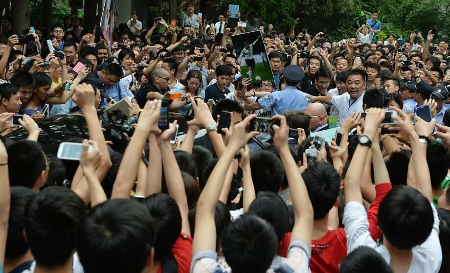 "A huge crowd gathers around the car (centre L) carrying football superstar David Beckham at Tonji University in Shanghai on June 20, 2013.  Football superstar David Beckham's visit to China turned ""chaotic"" on Thursday after at least five people were hurt in a stampede as fans rushed to see him, local media and an AFP photographer at the scene said.   AFP PHOTO / Peter PARKSPETER PARKS/AFP/Getty Images Photo: Peter Parks, AFP/Getty Images"