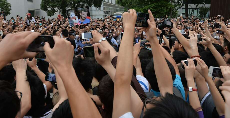 "A huge crowd gathers to see football superstar Beckham at Tonji University in Shanghai on June 20, 2013. Football superstar David Beckham's visit to China turned ""chaotic"" on Thursday after at least five people were hurt in a stampede as fans rushed to see him, local media and an AFP photographer at the scene said.   AFP PHOTO / Peter PARKSPETER PARKS/AFP/Getty Images Photo: Peter Parks, AFP/Getty Images"