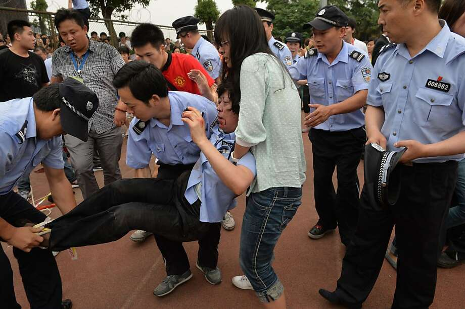 "A policewoman is carried after being crushed in a stampede to see football superstar David Beckham at Tonji University in Shanghai on June 20, 2013. Beckham's visit to China turned ""chaotic"" on June 20 after at least five people were hurt in a stampede as fans rushed to see him, local media and an AFP photographer at the scene said.