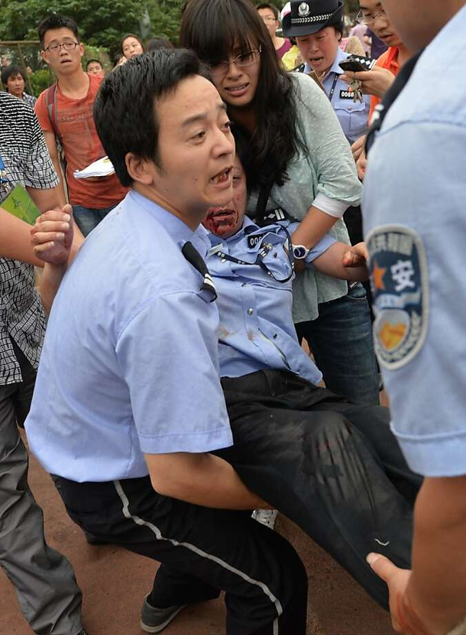 "A policewoman (C) is carried after being crushed in a stampede to see football superstar David Beckham at Tonji University in Shanghai on June 20, 2013. Beckham's visit to China turned ""chaotic"" on June 20 after at least five people were hurt in a stampede as fans rushed to see him, local media and an AFP photographer at the scene said.