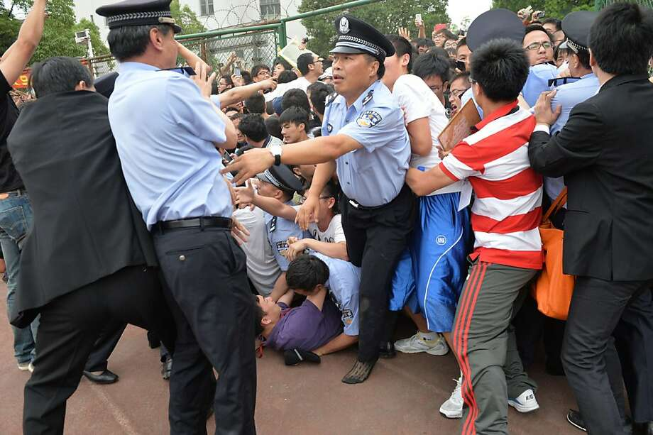 "People fall in a stampede to see football superstar David Beckham at Tonji University in Shanghai on June 20, 2013. Beckham's visit to China turned ""chaotic"" on June 20 after at least five people were hurt in a stampede as fans rushed to see him, local media and an AFP photographer at the scene said.    AFP PHOTO / Peter PARKSPETER PARKS/AFP/Getty Images Photo: Peter Parks, AFP/Getty Images"