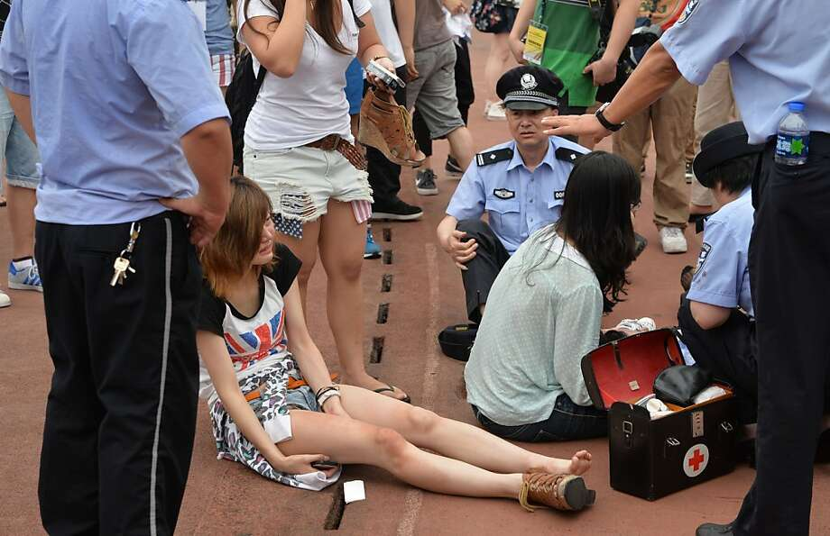 "A woman is treated for injuries after being crushed in a stampede to see football superstar David Beckham at Tonji University in Shanghai on June 20, 2013. Beckham's visit to China turned ""chaotic"" on June 20 after at least five people were hurt in a stampede as fans rushed to see him, local media and an AFP photographer at the scene said.