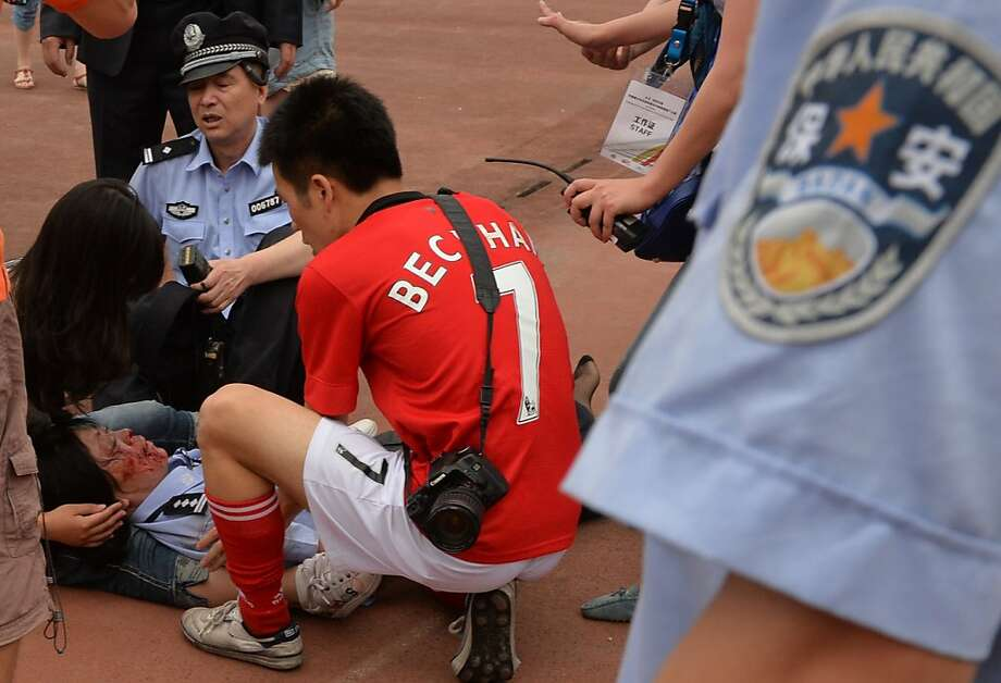 "A policewoman (L) is treated for injuries after being crushed in a stampede to see football superstar David Beckham at Tonji University in Shanghai on June 20, 2013. Beckham's visit to China turned ""chaotic"" on June 20 after at least five people were hurt in a stampede as fans rushed to see him, local media and an AFP photographer at the scene said.