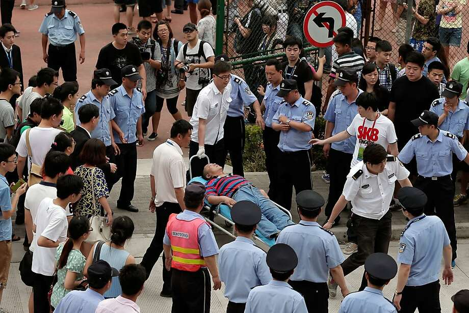SHANGHAI, CHINA - JUNE 20: An injured person is carried to an ambulance after a stampede during David Beckham's visit at Tongji University on June 20, 2013 in Shanghai, China. (Photo by Lintao Zhang/Getty Images) Photo: Lintao Zhang, Getty Images