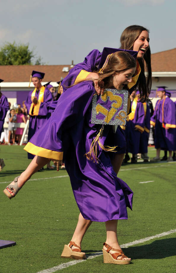 Emily Fitzpatrick carries Joely Mass after receiving their diplomas during the Westhill High School graduation ceremony in Stamford on Thursday, June 20, 2013. Photo: Jason Rearick / Stamford Advocate