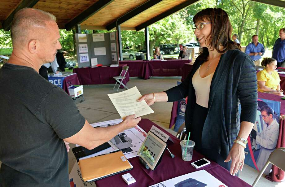 David Eveleth, left, of Green Island, hands a resume to Jennifer Angelopoulos of Cleveland Polymer Technologies during the Arsenal Business & Technology Partnership career fair in the Hudson Shores Park pavilion in Watervliet, NY, Thursday June 20, 2013.   (John Carl D'Annibale / Times Union) Photo: John Carl D'Annibale / 00022889A