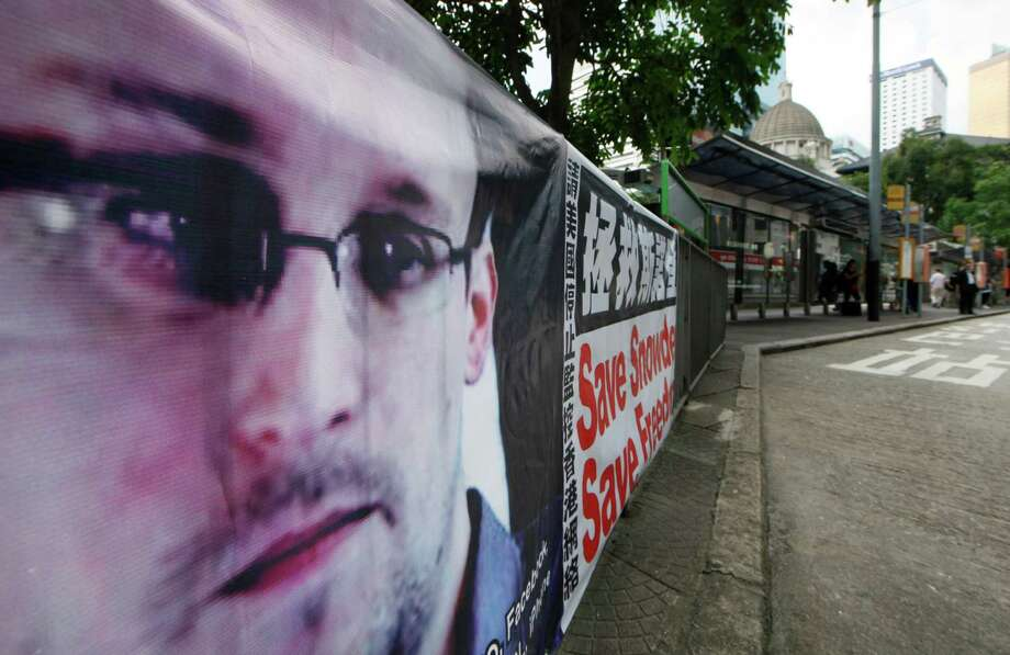 A banner supporting Edward Snowden, a former CIA employee who leaked top-secret documents about sweeping U.S. surveillance programs, is displayed at Central, Hong Kong's business district, Thursday, June 20, 2013. A WikiLeaks spokesman who claims to represent Snowden has reached out to government officials in Iceland about the potential of the NSA leaker applying for asylum in the Nordic country, officials there said Wednesday.  (AP Photo/Kin Cheung) Photo: Kin Cheung
