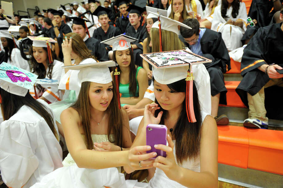 Kiersten Kellner, left, and Catherine Zhan ready themselves prior to the start of the Stamford High School graduation ceremony on Thursday, June 20, 2013. Photo: Jason Rearick / Stamford Advocate