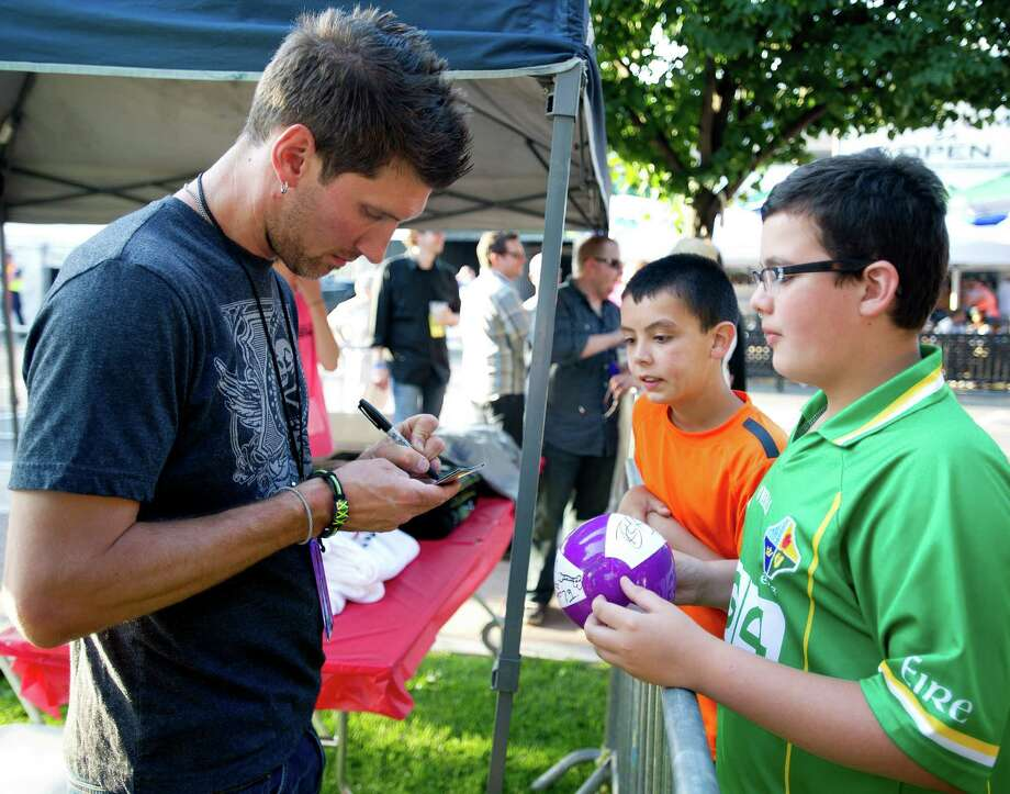 A member of the Brooks Young Band signs an autograph for Liam McDermott, 13, far right, and his brother, Aiden, 10, center, during Alive@Five in downtown Stamford, Conn., on Thursday, June 20, 2013. Photo: Lindsay Perry / Stamford Advocate