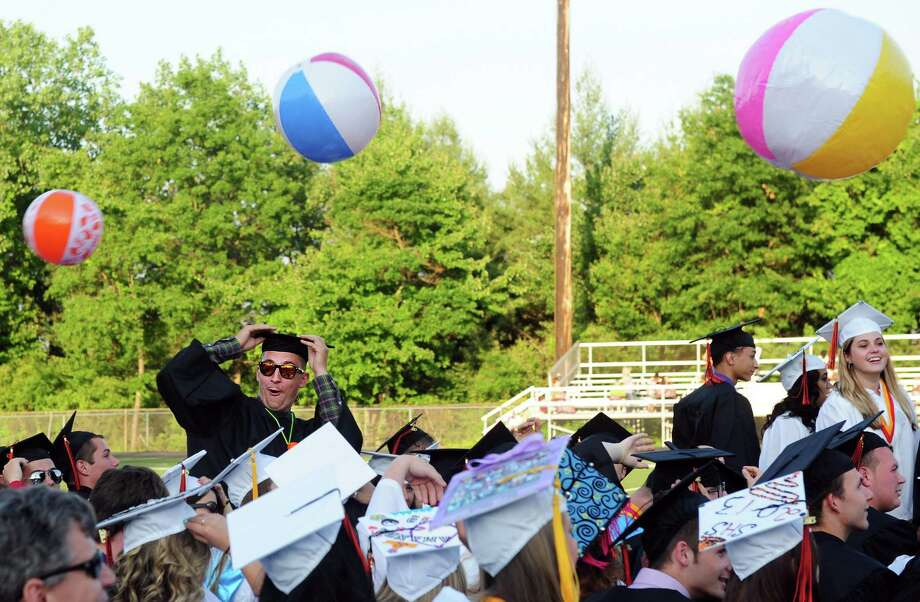 Graduate Scott Heins hangs onto his cap as a beach ball whizzes past during Shelton High School's commencement ceremony Thursday, June 20, 2013 at the school. Photo: Autumn Driscoll / Connecticut Post