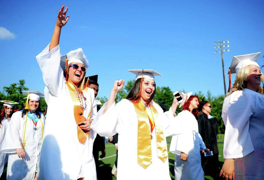 Graduates Julia Roshkind, left, and Chelsea Rodrigues march onto the field for Shelton High School's commencement ceremony Thursday, June 20, 2013. Photo: Autumn Driscoll / Connecticut Post